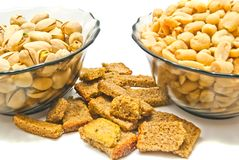 Two plates with tasty nuts and crackers. Two plates with nuts and crackers on white background Royalty Free Stock Photography