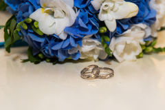 Two platinum wedding rings lie around the bride's bouquet of blue and white flowers. Stock Photography