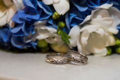 Two platinum wedding rings lie   bouquet of blue and white flowers. Royalty Free Stock Image