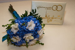 Two platinum wedding rings lie on a bouquet of blue and white flowers. The certificate of marriage. Stock Images