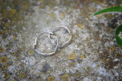 Two platinum wedding rings on old cement floor background. Close up photo of two wedding rings on cement floor background Royalty Free Stock Photos