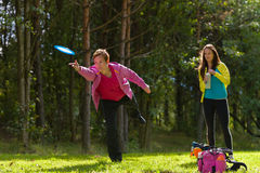 Two players. Woman throws a disc, friend waiting on background Stock Photo