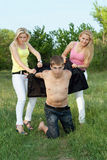 Two playful blonde and young man outdoors Stock Photography
