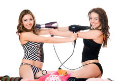 Two playful girlfriends with hair dryers. Isolated Stock Image