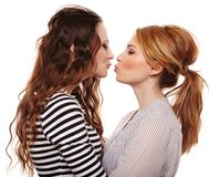 Two playful girlfriends hugging and kissing each other Stock Photos