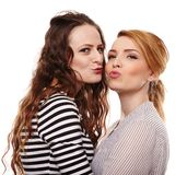 Two playful girlfriends hugging and kissing each other Royalty Free Stock Photo