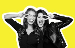Two playful girls gesturing v-sign near eyes on yellow. Magazine style collage of two foolish playful girls gesturing v-sign near winking eye, getting crazy at stock images