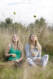 Two playful girls juggling outdoors Royalty Free Stock Photo