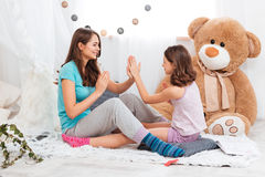 Two playful happy sisters sitting and playing together Royalty Free Stock Photo