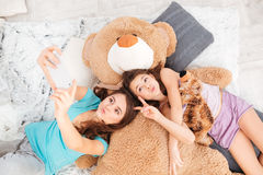 Two playful sisters sending kisses and making selfie using smartphone Stock Photography