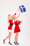 Two Playful Sisters Twins In Santa Claus Dresses Having Fun Royalty Free Stock Images
