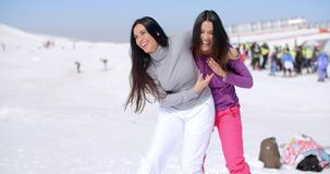 Two playful woman frolicking in the snow. Two playful attractive young woman frolicking in the snow at a winter resort laughing and joking as they goof around stock video