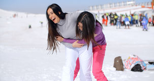 Two playful woman frolicking in the snow. Two playful attractive young women frolicking in the snow at a winter resort laughing and joking as they goof around Stock Image