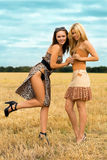 Two playful women. Standing in the field Royalty Free Stock Photo
