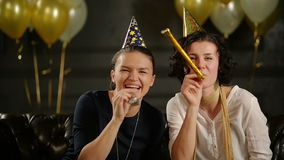 Two Playful Women are Blowing in Cheerleading Whistles During a Celebration. Closeup Portrait of Funny Brunettes in. Birthday Caps on Black Background with Air stock footage