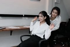 Two playful young Asian business woman playing together with chair in office royalty free stock image