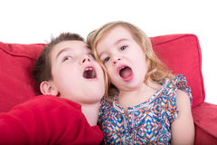 Two playful young children pulling faces. As an attractive brother and sister sit together on a red couch playing copycat with their mouths wide open Royalty Free Stock Image