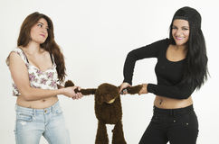 Two playful young girls with a teddy bear Stock Photos