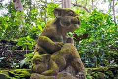 Two playing balinese dog sculpture covered in moss in Ubud, Bali stock images