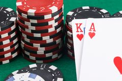 Two playing cards close-up on the background of poker chips on a green table royalty free stock image