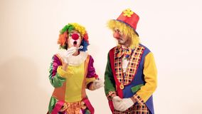 Two playing clowns having fun and trying to blow soap bubbles stock video