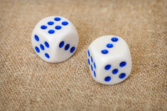 Two playing dices with blue points on brown canvas Stock Photos