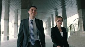 Two pleased smiling business people walking together along business center. Slow motion stock footage