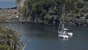 Two pleasure yachts sailing in nice harbor near green island, romantic vacation. Stock footage stock video footage