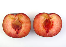 Two plum halves on white background. Royalty Free Stock Image