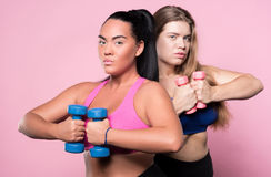 Two plump women exercising with dumbbells Royalty Free Stock Images