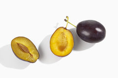 two plums one whole one halved on white background Royalty Free Stock Image
