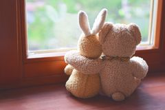 Best friends two plush toys on windowsill royalty free stock image