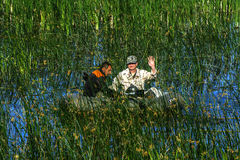 Two poachers on a rubber boat catch fish in the net. Zhitomir. Ukraine, June 16, 2017 royalty free stock images