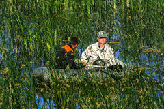 Two poachers on a rubber boat catch fish in the net. Zhitomir. Ukraine, June 16, 2017 stock photos