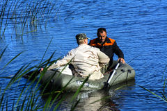 Two poachers on a rubber boat catch fish in the net. Zhitomir. Ukraine, June 16, 2017 royalty free stock photos