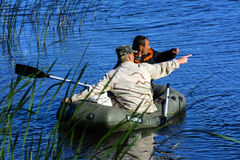 Two poachers on a rubber boat catch fish in the net. Zhitomir. Ukraine, June 16, 2017 royalty free stock image