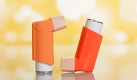 Two pocket inhalers on yellow. Two small orange pocket inhalers on bright beautiful yellow background Stock Photos