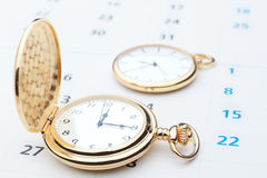 Two pocket watch against the background of the calendar. Stock Images