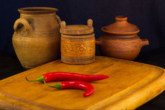 Two pods of red hot pepper on a black background is a jar ceramic pots Stock Images