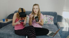 Two podurgi fun house. Playing in virtual reality helmet, eat food and watch television. Pajama party girlfriends stock video footage