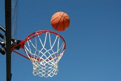 Two Points?. Basketball in flight towards outdoor basket on beautiful day Royalty Free Stock Photos