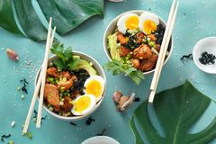 Two poke bowl fried rice chicken fillet eggs top view Asian food royalty free stock images