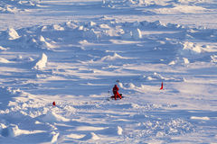 Two polar scientists working on an ice floe. Two polar scientists in red polar clothing working on ice cores over an ice floe Royalty Free Stock Image