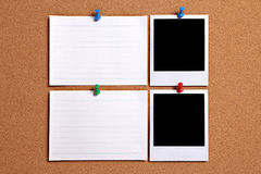 Two polaroid style photo frames with blank white note cards pinned to cork notice board, copy space stock photo