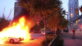 Two police cars burning at riot - HD 1080p. Two police cruisers Crown Victoria on fire at a riot with police making loud announcements in pa system.NHL Stanley stock footage