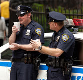 Two police officers while drinking a cup of coffee in NYC. Stock Images