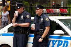 Two police officers while drinking a cup of coffee in NYC. Royalty Free Stock Images