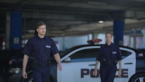 Two police officers getting out from car and going to accident place, danger. Stock footage stock footage