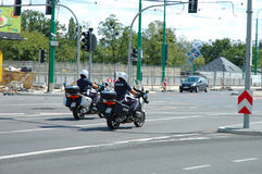 Two police officers on motorcycles on street in Poznan, Poland. Poznan, Poland - July 13, 2014: Two unidentified polish police officers driving on motorcycles on royalty free stock photo