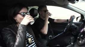 Two police officers sitting in car during break. Policewoman with policeman relaxing in patrol car during break Stock Photos